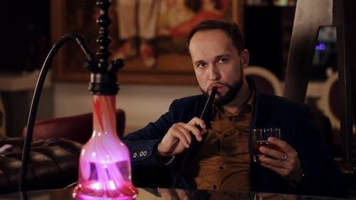 Young Intelligent Man Smoking Hookah