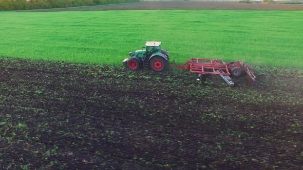 Thumbnail for Tractor Plowing The Field, The Young Wheat Is Processed At The Fertilizer