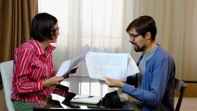 Young Couple Fighting Over Bills and Home Budget in the Living Room