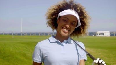 Cheerful Female Golfer Walking With Golf Club