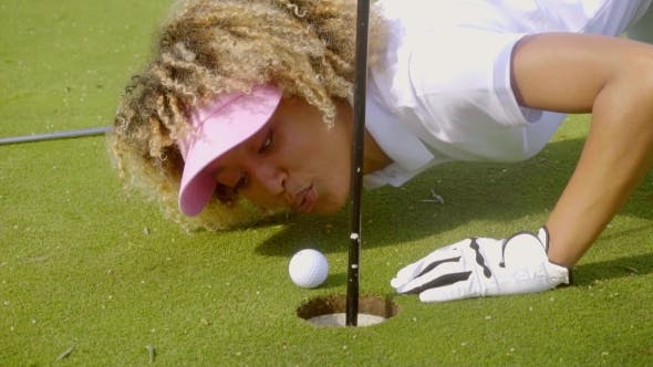 Thumbnail for Young Woman Blowing Her Golf Ball Into The Hole