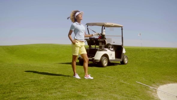 Cover Image for Young Woman Golfer Standing Above a Sand Bunker
