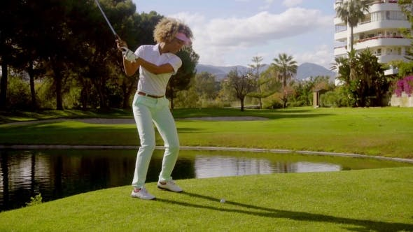 Thumbnail for Young Woman Golfer Playing a Shot Near a Lake