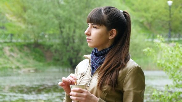 Thumbnail for Portrait Of Attractive Woman Thoughtfully Looks Out Over River And Holding Cup Of Tea