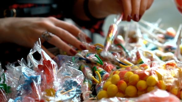 Thumbnail for Woman's Hand Picking Up Messy Colorful Candies