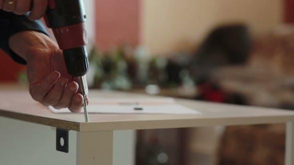 Thumbnail for Mann montiert Möbel mit einem Schraubenzieher