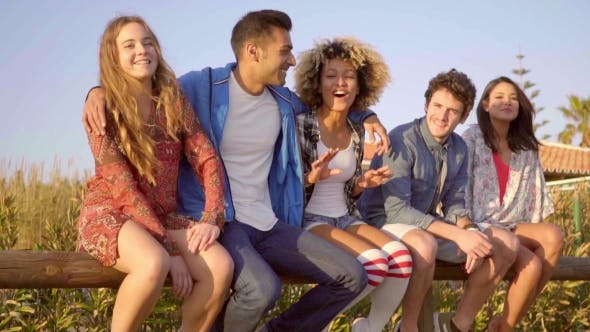 Thumbnail for Junge Leute sitzen auf Holzzaun.
