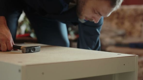 Thumbnail for Man Assembles Parts Of Furniture Using a Hammer