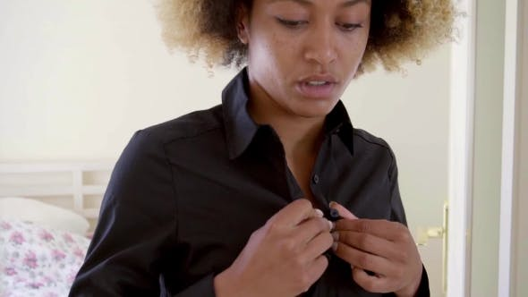 Thumbnail for Sleepy Black Woman Buttons Her Blouse By The Bed