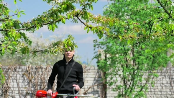 Thumbnail for Male Worker With String Lawn Trimmer