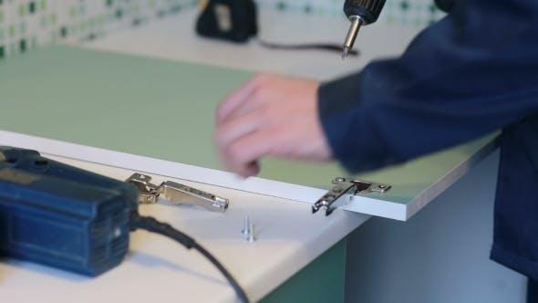 Thumbnail for Man Assembles Furniture Using a Power Screwdriver