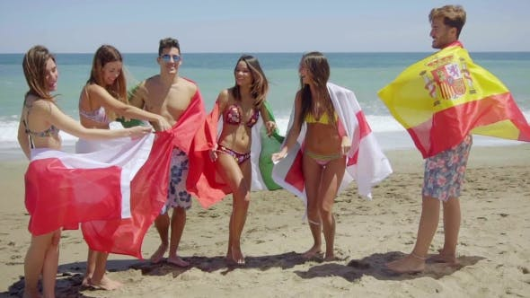 Thumbnail for Group Of Friends In Swim Suits With Flags At Beach