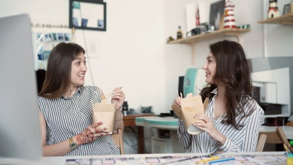 Thumbnail for Smiling Young Businesswomen Having Lunch At Table In Office