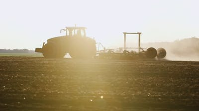 Tractor Silhouette At Sunset. The Tractor Sows Field