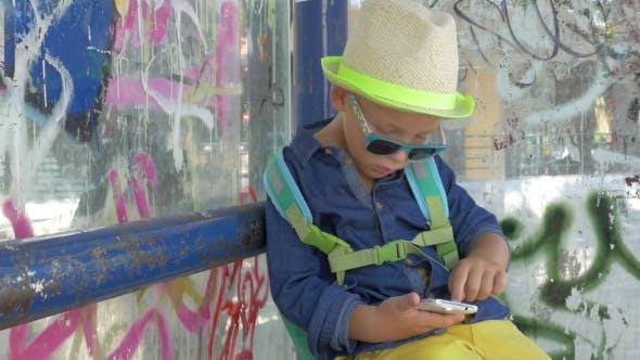 Junge mit Smartphone bei Grungy City Bushaltestelle
