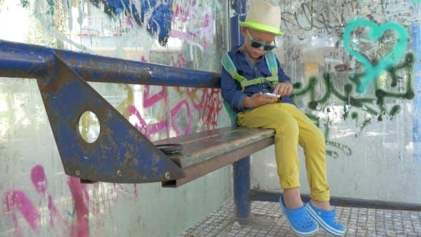 Kind mit Smartphone auf Grungy Bushaltestelle