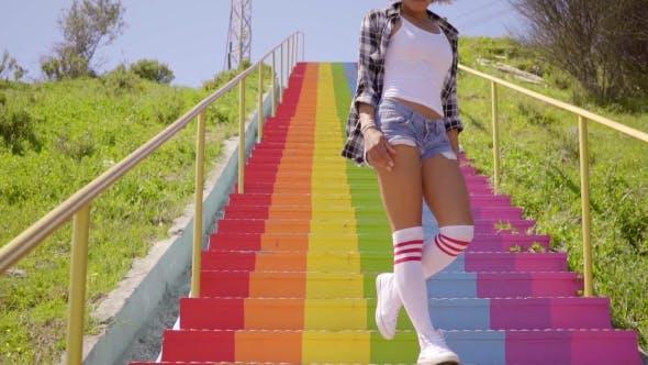 Thumbnail for Young Woman Walks Down The Colorful Stairs.