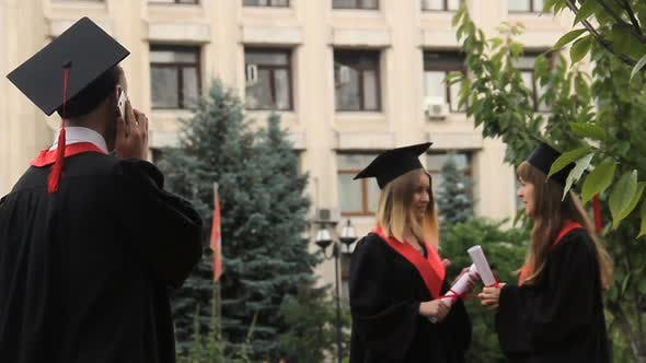 Thumbnail for Smiling Student Listening to Greetings Over Smartphone on Graduation Day