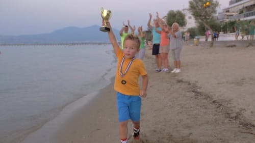 Family Members Applauding To Little Champion Boy
