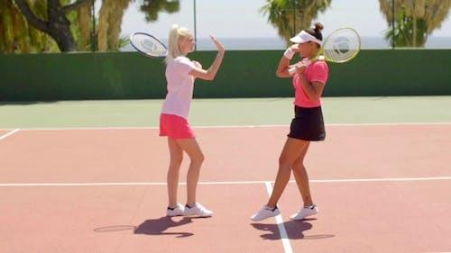 Tennispartner laufen, um einander zu gratulieren