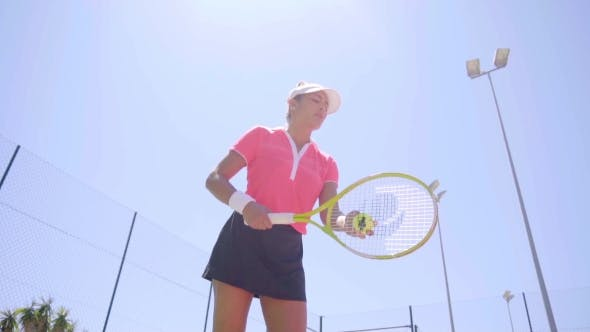 Thumbnail for Low Angle View On Woman Bouncing Tennis Ball