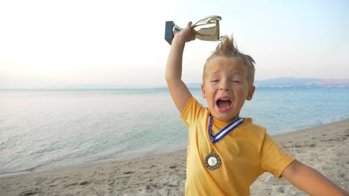 Little Winner Boy With Medal And Cup