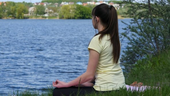 Thumbnail for Young Woman Meditating and Listening Music on Smartphone in Headphones in Lotus Position.