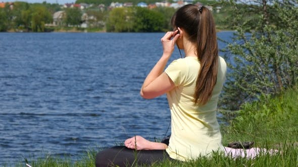 Thumbnail for Young Woman Putting Earphones In Her Ears And Meditating In Lotus Position