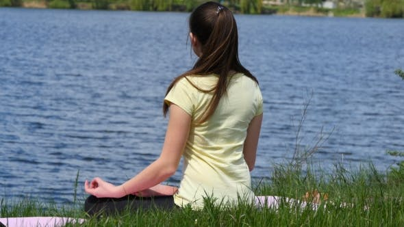 Thumbnail for Young Woman Relaxing Meditating On The Beach Beside The River