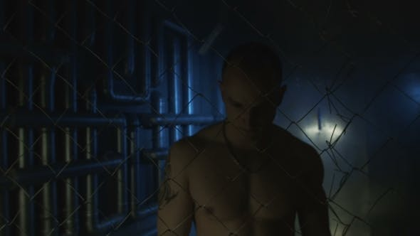 Thumbnail for Topless Man With Metal Chain Beyond The Fence
