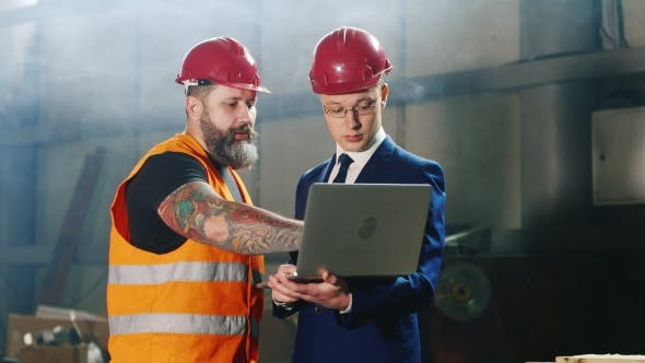 Thumbnail for Engineer In Helmet And Construction Worker Working With Laptop