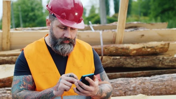 Thumbnail for Brutal Builder With a Beard And Tattoos Sitting On The Logs, Using a Mobile Phone