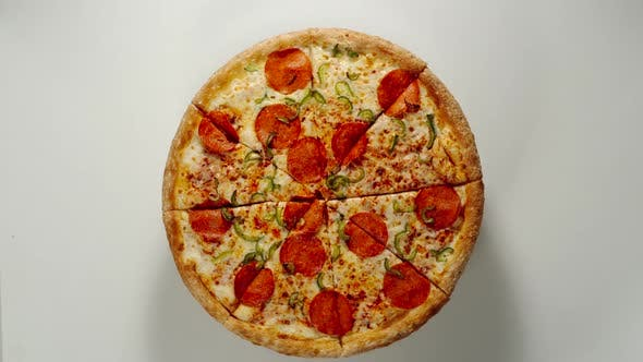 Thumbnail for Whole Circle Of Big Pizza Is Rotating On A White Surface