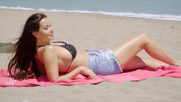 Thumbnail for Trendy Young Woman Sunbathing On The Beach