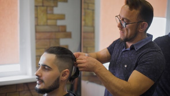 Thumbnail for Lumberjack Style. Male Barber in Plaid Shirt Combing Hair of a Male Client at Barbershop