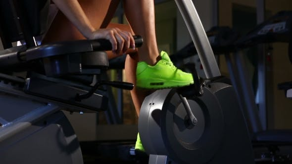 Cover Image for Female Legs Riding At Stationary Bike In The Gym