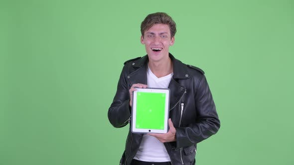 Thumbnail for Happy Young Rebellious Man Showing Digital Tablet and Looking Surprised