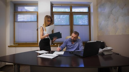 Attractive Girl Secretary Brings Documents To Sign. Her Boss Respectable, Gray-Haired Man