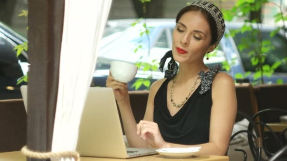 Thumbnail for Woman Working On Laptop In Cafe And Answering The Call
