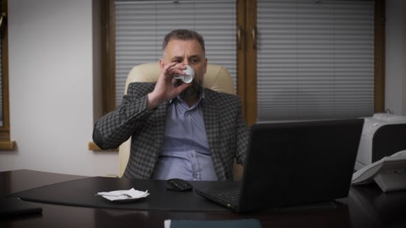 Chief In His Office Working With a Laptop And Drinking Coffee