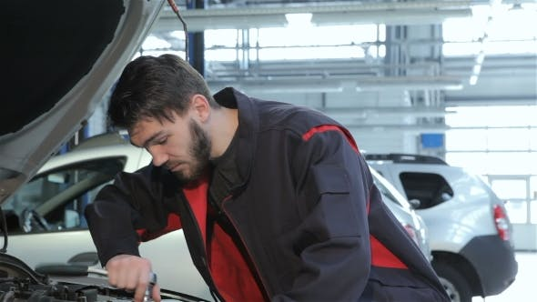 Thumbnail for Mechanic Twists Wrench Under Car Hood  At The Car Service