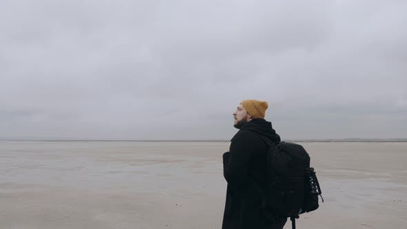 Thumbnail for Happy Thoughtful Young Man with Backpack Looking Around, Lost Alone at Endless Cloudy Low Tide Sandy