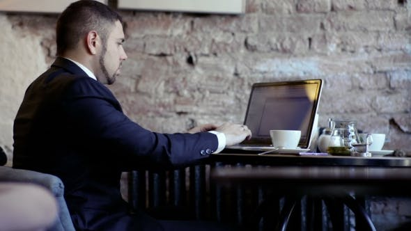 Thumbnail for Businessman Works With Laptop In The Cafe