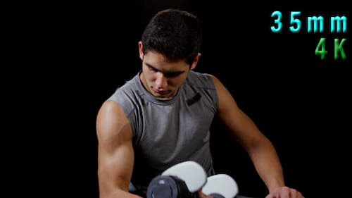 Young Man Working On Biceps With Dumbbells 20