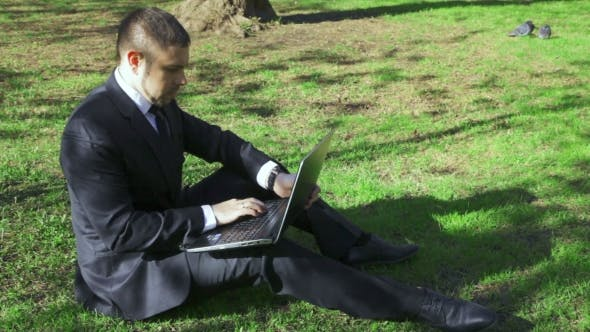 Thumbnail for Businessman Works With Laptop In The City Park