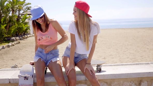 Thumbnail for Two Laughing Friends In Shorts Sitting Near Beach