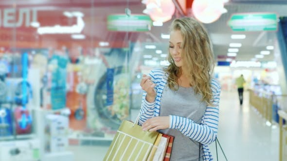 Cover Image for Happy Young Woman With Shopping Bags Goes Along Storefronts Shopping Center