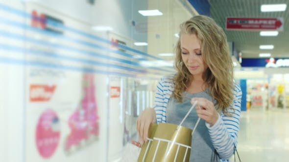 Thumbnail for Young Model Looks a Woman With Shopping Bags Goes To The Mall