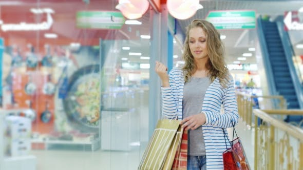 Thumbnail for Attractive Young Woman With Many Shopping Bags Goes Along Storefronts Shopping