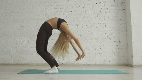 Thumbnail for Beautiful Young Woman Doing Yoga Exercise, Stretching, Standing In Bridge Pose